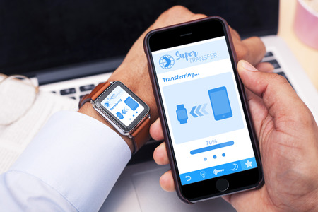 transference: Smartphone and Smartwatch Stock Photo