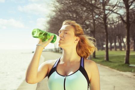 Aptitud de la mujer corredor tomar la bebida de agua o energía