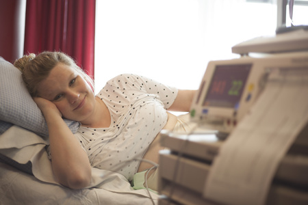 Pregnant woman in hospital and fetal heartbeat monitor