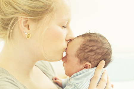 Mother kissing her newborn child