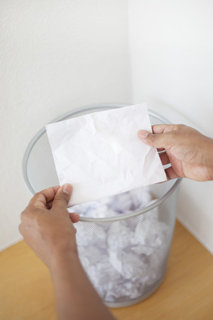 garbage can: Man holding blank paper in front of the garbage can. Concept with copy space Stock Photo