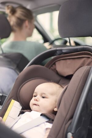 child seat: Mother driving, with her baby boy in a child seat