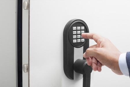 Businessman's hand entering security system code