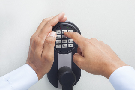 Interracial businessman hand entering security system code Imagens