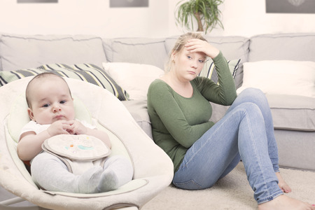 Young new mother suffering from postpartum depression 스톡 콘텐츠