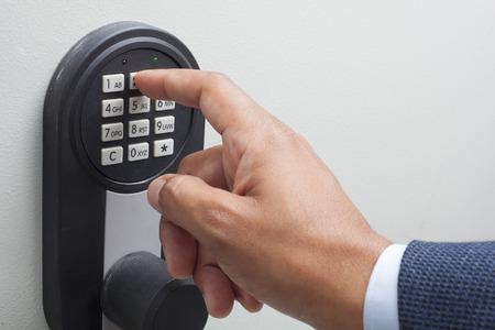 erracial businessman hand entering security system code Imagens