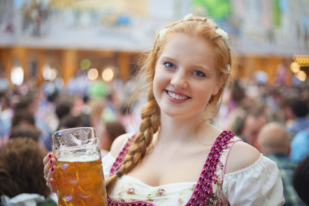 Portrait of cheerful young woman wearing traditional dirndl and holding the 1 liter beer stein at Oktoberfest