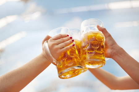 Raised beer steins at Oktoberfest toasting