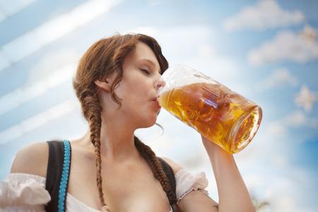 biergarten: Young German woman drinking beer inside a tent at Oktoberfest Stock Photo
