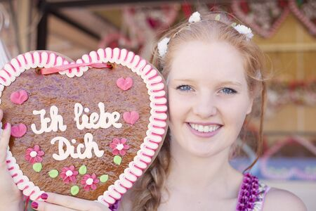 German girl holding a traditional Oktoberfests gingerbread heart