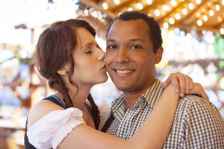 Junger Mann auf der Wange geküsst von deutschem Mädchen auf Oktoberfest