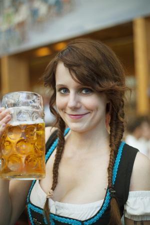 Porträt von fröhliche junge deutsche Frau mit traditionellen Dirndl und halten einen Bierkrug in einem Zelt auf Oktoberfest Lizenzfreie Bilder
