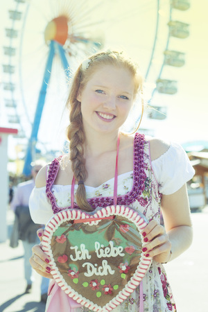german girl: German girl wearing a Dirndl and holding a traditional Oktoberfests gingerbread heart Stock Photo
