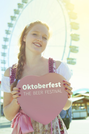 german girl: German girl holding an traditional Oktoberfest heart with copyspace