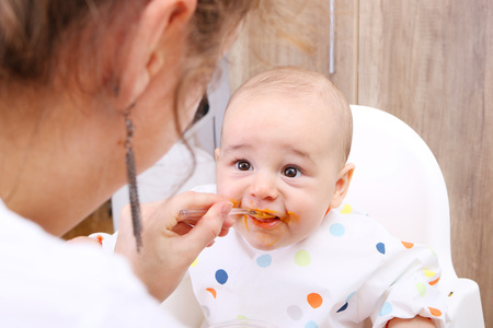 Mother feeding her baby solids