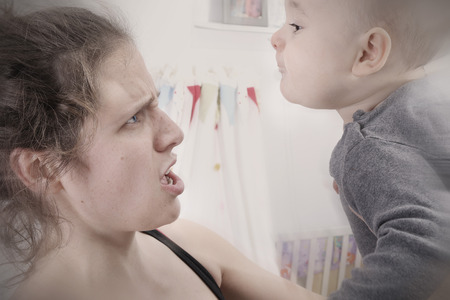 Mother suffering from postpartum depression shakes and screams at her baby Archivio Fotografico