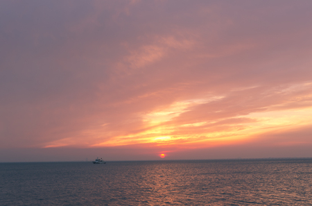 Fire burning clouds by the sea 写真素材
