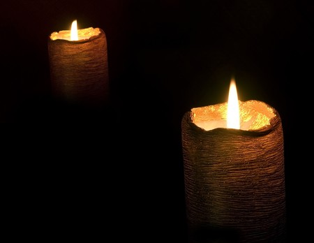 pair of gold mystical burning candles on a black background