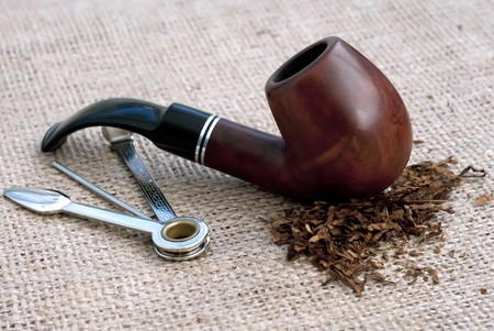 Tobacco pipe on sacking background with tobacco and accessory photo