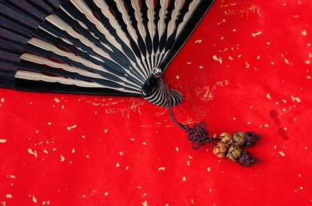 Chinese bamboo fan on red paper background Stock Photo - 8542947