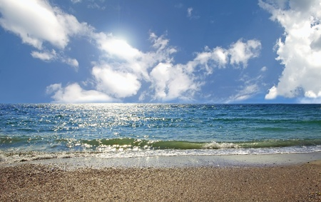 Sea coast with blue sky and white clouds Stock Photo
