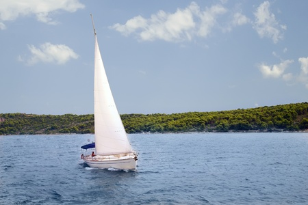 Adriatic seascape with white sailboat and blue sky