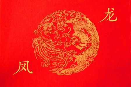 Chinese ornament dragon and phoenix on red paper Фото со стока