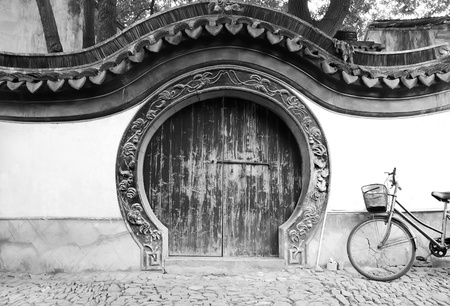Wooden traditional chinese round gate and bicycle
