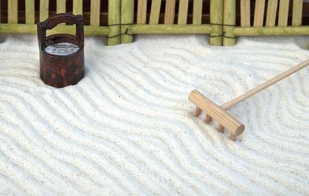Traditional japanese zen garden with rake and bucket photo
