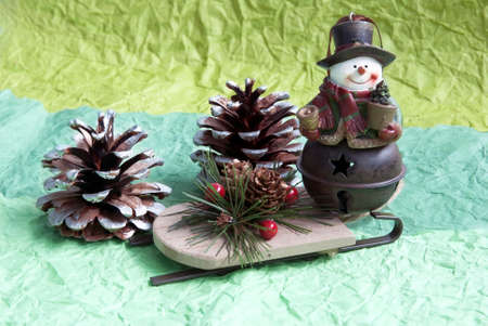 Snowman with fir-cone and sled on green background