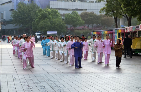 chuan: China, Shanghai -  november 5, 2013: People doing morning exercises tai chi chuan on pedestrian street Nanjing road in Shanghai on 5th of november 2013 China. Tai Chi Chuan - one of the most popular sports in China.