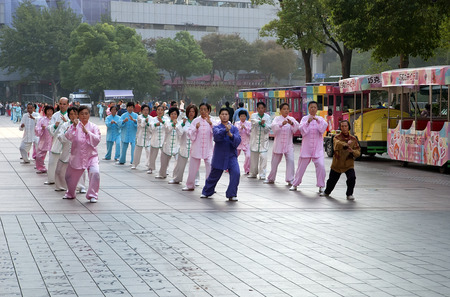 China, Shanghai -  november 5, 2013: People doing morning exercises tai chi chuan on pedestrian street Nanjing road in Shanghai on 5th of november 2013 China. Tai Chi Chuan - one of the most popular sports in China.