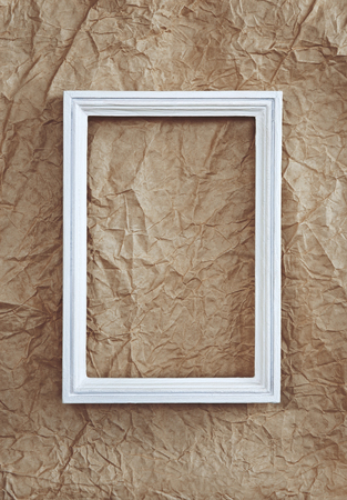 Empty white frame on beige wrinkled paper background
