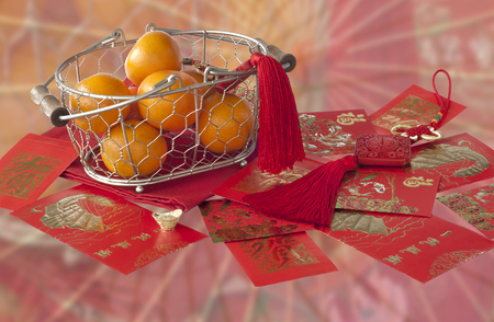 Mandarins in basket and red envelopes with good luck wishes on blurred background Stock Photo