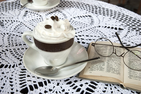 Cup of coffee with cream on the table and book