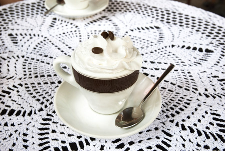 Cup of coffee with cream on the table Stock Photo