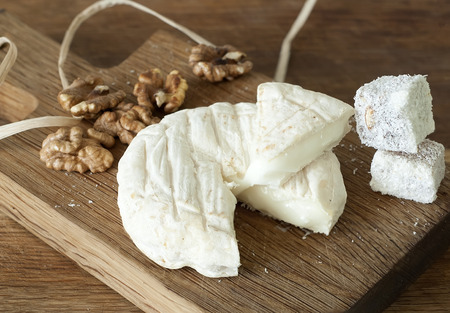 Delicious french goat cheese with walnut and lokum on wooden board
