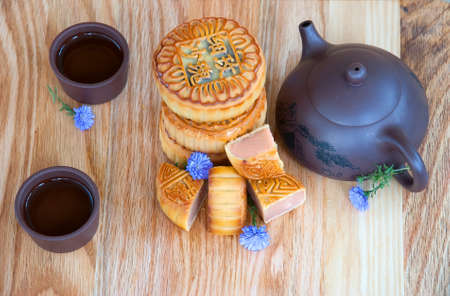 Traditional chinese moon cakes on board for mid autumn festival. Hieroglyphs on moon cakes mean the components of their inner filling - crystal sugar, rose hip, gold wire, fine sand, date. Zdjęcie Seryjne