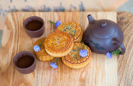 Traditional chinese moon cakes on board for mid autumn festival. Hieroglyphs on moon cakes mean the components of their inner filling - crystal sugar, rose hip, gold wire, fine sand, date.