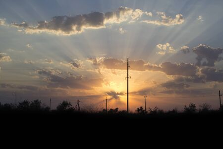 Sunny sunset above the ground. Incredible landscape of sunny sunset in the sky sun rays piercing clouds. Banco de Imagens
