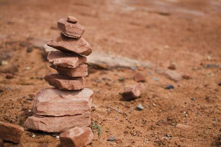 Orange cairn closeup. Traveling in america, national park in arizona, desert. Trekking touristic. Sign of a visited place. A lot of terracotta pebbles, a stone tower.