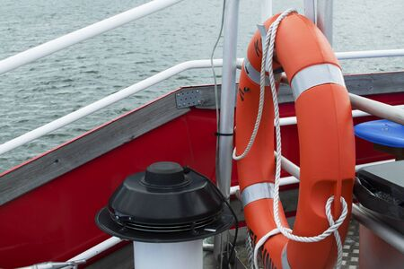 Orange lifebuoy on a boat for the safety of people. Rescue props on a boat. A floating boat at sea, security measures. 版權商用圖片