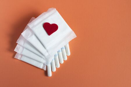 Feminine hygiene during menstruation. Menstrual cycle. Hygiene products for women. Pads and tampons with, red heart on a orange background. Gentle body care. Place for text.