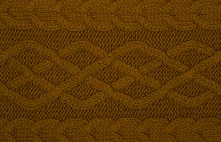 Knitted texture with braids of dark ginger color. Scarf made of wool yarn. Warm stylish clothing accessory for the winter. Handmade concept of natural woolen products. Layout for design, copy space.
