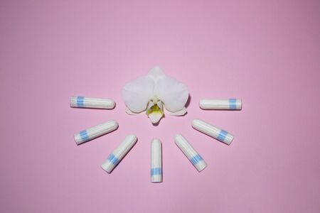 The concept female intimate hygiene. Cotton tampons on a pink background. Menstrual cycle. Critical days in women. Template for design or social advertising. Orchid flower. Place for text.