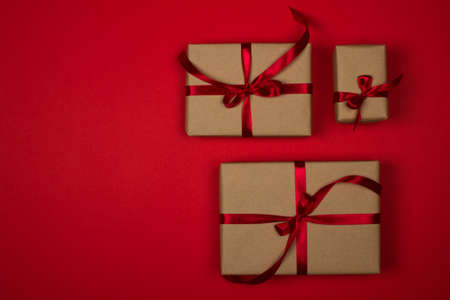 Gift box set on a red background. Satin burgundy ribbon, bow, box wrapped in craft paper. Luxury gift, place for text. Holidays concept. View from above, layout for design. Concert of holiday shopping.