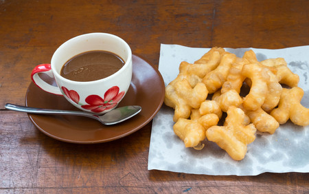 coffee on wooden table with  deep-fried dough stick photo