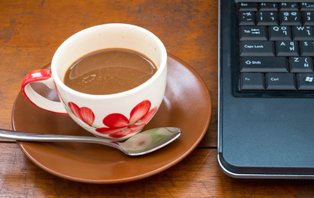 coffee on wooden table with laptop photo