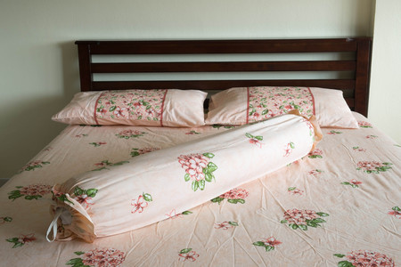 Wooden bed and flower pillow photo