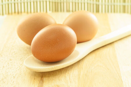 eggs on wooden ladle and chopping block photo